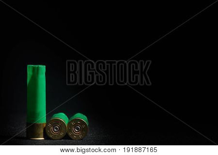Used Casings From Shotgun Ammunition Are Located In The Left Side Of The Frame, Black Background