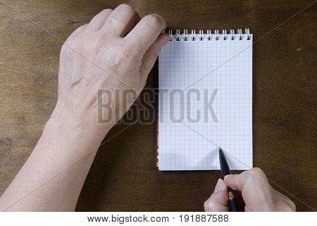 Hand writing on empty notepad on a wooden table