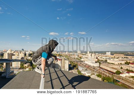 Roofer sitting on a railing at the edge of the roof. Extreme life. Courage and adrenaline. Parkour and Roofing.