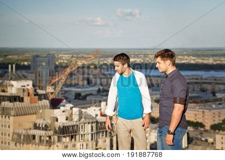 Two roofers on the roof of a high-rise building admire the view of the city. Courage and adrenaline. The men are looking down.