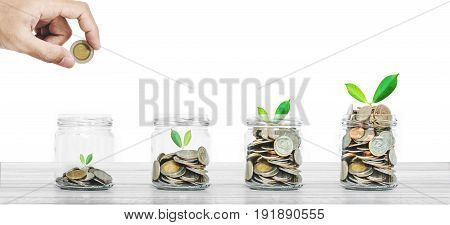 Hand putting coin in glass bottles with plants glowing, Saving money , investment and economize concepts