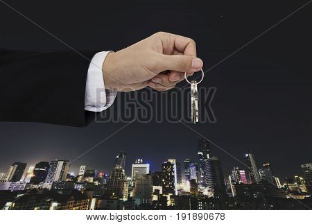 Hand holding keys with city background, real estate and property concepts
