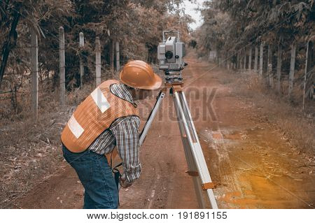 Surveyor or Engineer making measure by Theodolite on the street in a field.