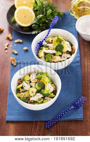 Chicken with sprouts walnuts parmesan in white bowls