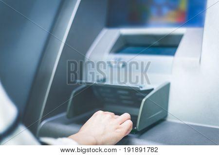 Woman hand touching cash machine-ATM,close up view.