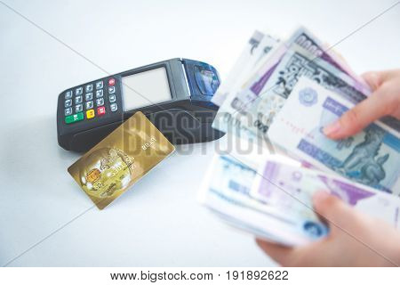 cash and card payment with chip and pin machine in shop.