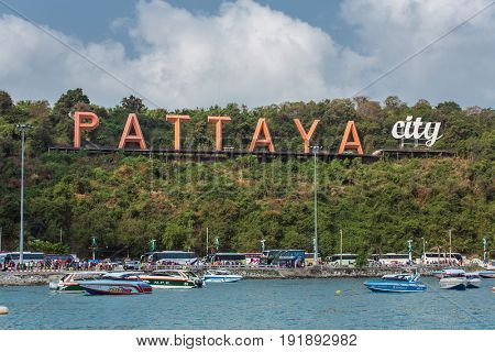 Pattaya, Thailand - March 7, 2017 : The famous Pattaya city sign on the hill at Pattaya bay with commerical boats and speed boats.