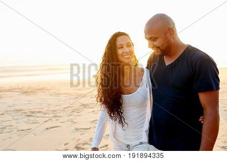 Cheerful adult African-American couple taking walk through sandy beach at seaside in the evening.