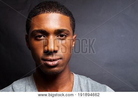 Serious African American man standing against a dark background.