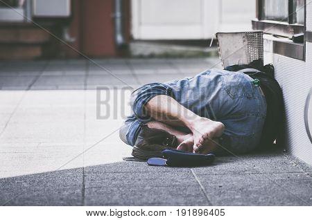 Homeless. Homeless man sleeps on the street, in the shadow of the building. Social documentary.