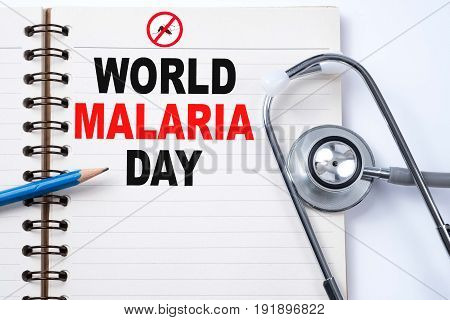 Stethoscope on notebook and pencil with WORLD MALARIA DAY words as medical concept.