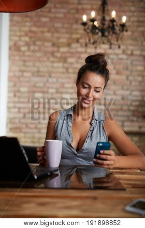 Young woman sitting at home, using mobilephone drinking tea.