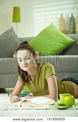 Teenage student girl lying on floor at home doing homework. Looking down, smiling.