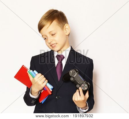 Boy in a suit with textbooks and a game joystick
