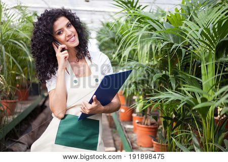 Female clerk talking on the phone in a greenhouse