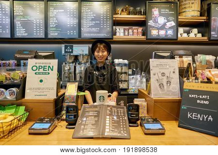 SEOUL, SOUTH KOREA - CIRCA MAY, 2017: indoor portrait of a worker at Starbucks Reserve. Starbucks Corporation is an American coffee company and coffeehouse chain.