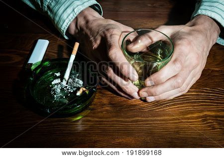 Hands of alcoholic man holding a glass with alcohol drink with smoking cigarette in the ashtray. Alcohol and cigarette addiction. Depression. Loneliness. Sadness.