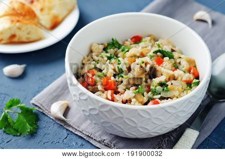 Red bell pepper eggplant cilantro rice on a grey background