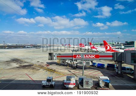 ISTANBUL TURKEY - October 2013: Airplanes at Istanbul Ataturk Airport in Istanbul Turkey. A view from Istanbul Ataturk airport. Baggage cart in the foreground.