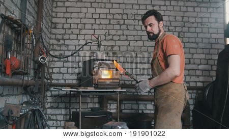 Young muscular man working on a blacksmith with metal, wide angle