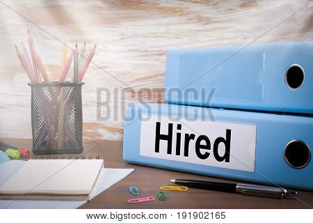 Hired, Office Binder on Wooden Desk. On the table colored pencils, pen, notebook paper.