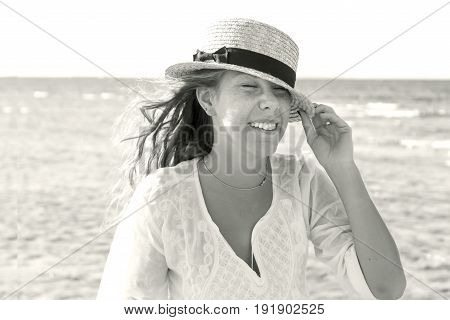 A young woman in a straw hat fervently laughing against the background of the sea a large portrait in retro style black and white. The concept of a young and healthy lifestyle.