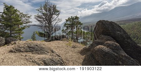 Huge boulders on top of a wooded hill.