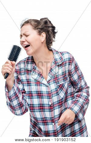 A Girl In Pajamas Loves A Song To Sing, Instead Of A Microphone A Hairbrush On A White Background