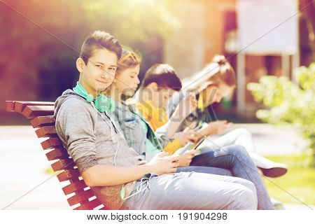 technology, internet and people concept - happy teenage boy with tablet pc computer and headphones outdoors