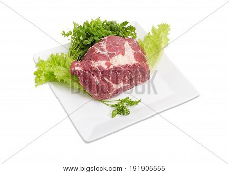 Piece of a fresh uncooked pork neck on the lettuce leaves and bundle of the parsley on the white square dish on a light background