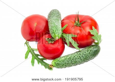Three red tomatoes different sizes two cucumbers and arugula leaves closeup on a light background