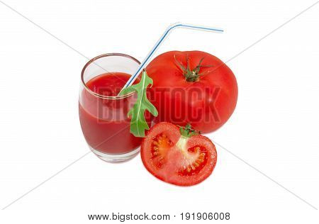 One whole and one half of the fresh ripe tomatoes tomato juice in glass with bendable drinking straw and arugula leaf on a light background