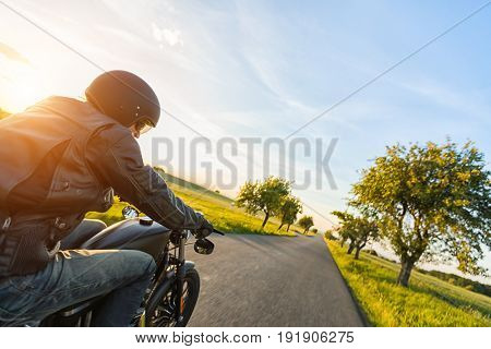 Dark motorbiker riding high power motorbike in nature with beautiful sunset light. Travel and transportation. Freedom of motorbike riding