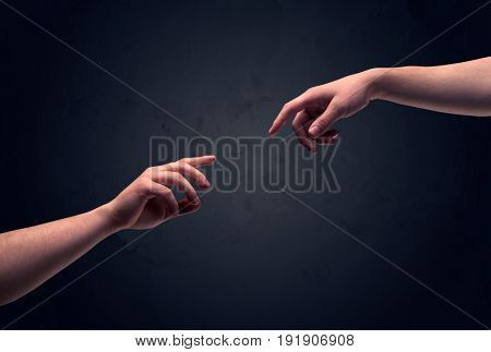 Two male hands reaching out to one another, almost touching, in front of dark clear empty background wall concept
