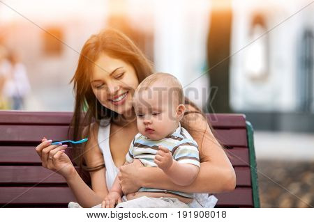 Baby feeding spoon by mother in park outdoor. Weaning in first weeks. Mom and eating child summer on bench. Good appetite by baby food with foster mother . Color tone on shiny sunlight background.