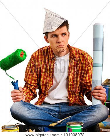 Repair home man holding paint bank. Tired mad male in newspaper cap renovation apartment. Paint bank and brush in hand. Choice of materials for construction and hire professional builder concept.