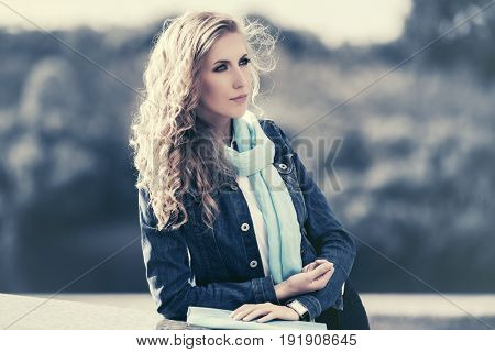 Young blond woman with long curly hairs walking outdoor. Stylish fashion model in blue scarf and denim jacket