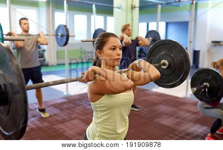 fitness, sport, training, exercising and lifestyle concept - group of people with barbells doing shoulder press in gym