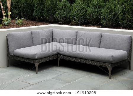 Horizontal image of comfortable gray couch, set in stone courtyard