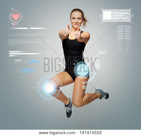 sport, fitness and technology concept - young woman in black sportswear jumping and showing thumbs up