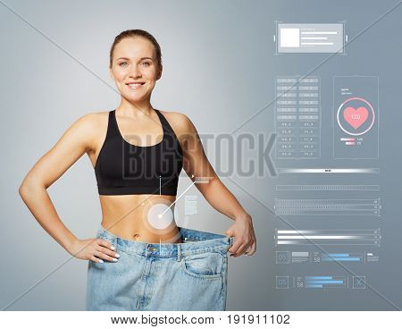 healthy lifestyle and technology concept - young slim sporty woman in large size pants showing weight loss result