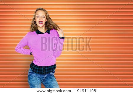 people, hairstyle and fashion concept - happy young woman or teen girl in casual clothes touching hair over orange ribbed wall background