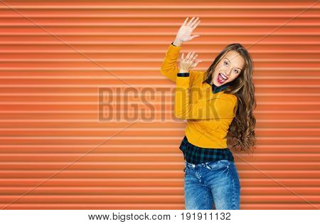 people, style and fashion concept - happy young woman or teen girl in casual clothes having fun and applauding over orange ribbed wall background