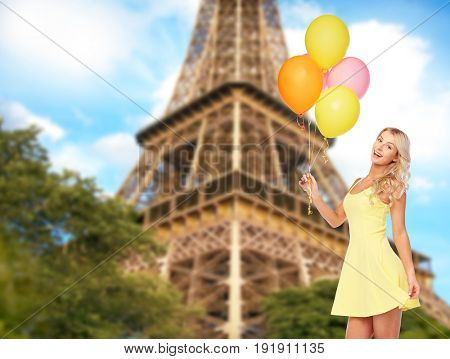people, tourism and birthday party concept - happy young woman or teen girl in dress with helium air balloons over eiffel tower background