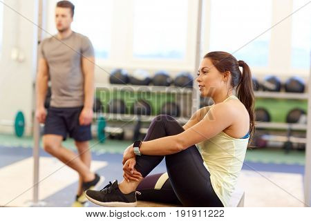 sport, fitness, lifestyle and people concept - man and woman with heart rate tracker in gym