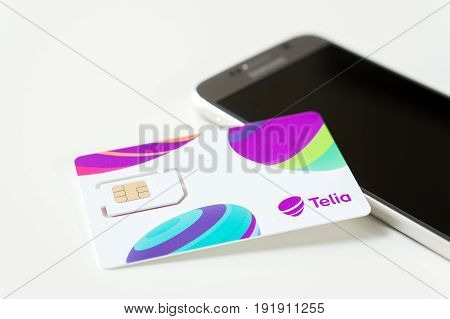JYVASKYLA, FINLAND - JUNE 19, 2017: Brand new Telia sim card on smartphone on table. Telia is a telephone company and mobile network operator in Europe. Illustrative editorial.
