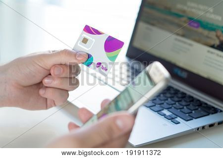 JYVASKYLA, FINLAND - JUNE 19, 2017: Man holding new Telia sim card and smartphone with laptop at home. Telia is a telephone company and mobile network operator in Europe. Illustrative editorial.