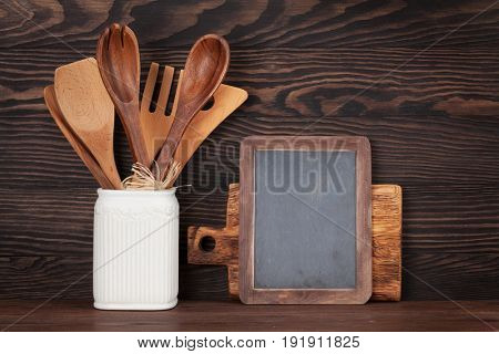 Kitchen utensils in front of wooden wall and blank chalkboard for your text