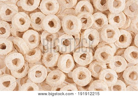 Beige rings corn flakes closeup background. Cereals texture.