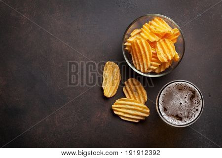 Lager beer and potato chips on stone table. Top view with copy space